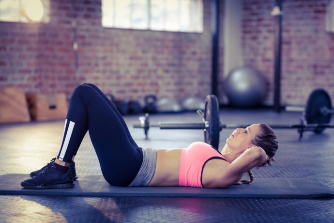 Woman doing abdominal crunches on exercise mat